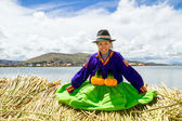 Sitting girl on a floating Uros island, Titicaca — Stock Photo