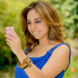 Young beautiful brunette lady browsing her phone — Stock Photo