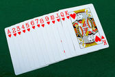 Playing cards red deck on the green background — Stock Photo