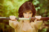 Woman with sword at forest — Stock Photo