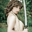 Gorgeous young woman holding a sword in the park — Stock Photo