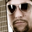 Musician and his guitar Face and strings — Stock Photo
