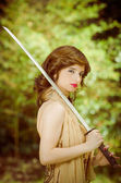 Pretty girl in a dress with vintage sword outdoors — Stock Photo