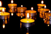 Group of burning candles on black background. — Foto Stock