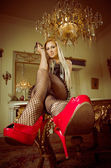 Blonde lying on a table with heels and stockings — Stock Photo