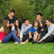 Stock Photo: Happy group of students sitting at the park