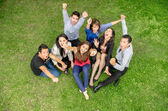 Group of friends holding hands up outdoors — Stock Photo