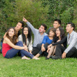 Happy group of students sitting at the park — Stockfoto