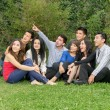 Happy group of students sitting at the park — Foto Stock