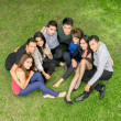 Happy group of students sitting at the park — Stock Photo