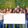 Group of friends holding blank sign outside — Stok fotoğraf