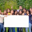 Group of friends holding blank sign outside — Stockfoto