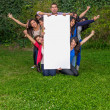 Group of friends holding blank sign outside — Stock Photo #27438421