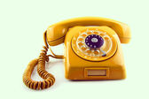 Old Orange telephone with rotary dial — Stock Photo
