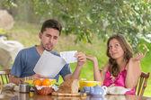 Casal tomando café brigando por contas em casa com jardim no fundo — Fotografia Stock