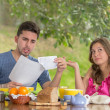 Couple having breakfast fighting over bills at home with garden in the background — Stock Photo