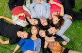 Group of friends laying down in park — Stok fotoğraf