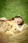 SLEEPING BEAUTY lying on the forrest with a rose — Stock Photo