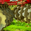 Disk harrow sitting in Green plantation — Stock Photo