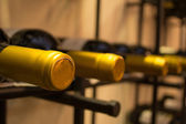 Wine bottles stacked on racks shot with limited depth of field — Stock Photo