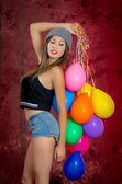 Young woman with balloons around her, studio shot — Stock Photo