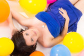 Sexy young woman lying on floor among balloons — Stock Photo