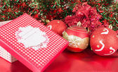 Christmas gift with red ornament balls — Stock Photo