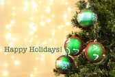 Christmas de-focused lights with tree and happy holidays — Stock Photo