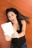Happy young woman lying using tablet pc at home — Stock Photo
