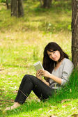 Happy young woman with digital tablet sitting on grass in park — Stock Photo