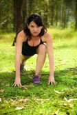 Young woman stretching before exercise in the park — Stock Photo