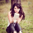 Woman using tablet outdoor on grass — Foto de Stock