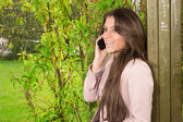Happy young woman on cell phone in spring park — Stock Photo
