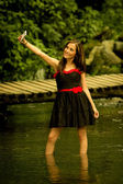 Beautiful young woman taking a selfie in the lake — Stock Photo