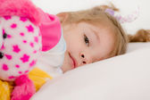 Adorable little girl going to sleep in the bed — Stock Photo