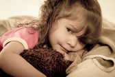 Sad little girl lying in bed colortoned — Stockfoto