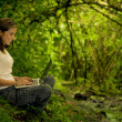 Woman in the forest using a laptop — Stockfoto