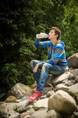 Man drinking water outdoors in the jungle — Stock Photo