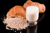Milk oatmeal and bread in a dark background — Stock Photo