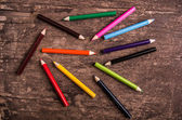 Color pencils scattered on wood background — Stock Photo