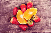 Strawberries and oranges on wood — Stock Photo