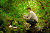 Man using tablet  and personal computer in the jungle — Stock Photo