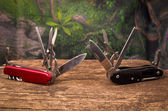Several swiss army knifes on wood in the rainforest — Stock Photo