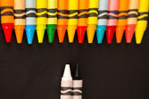 Colored versus black and white crayons — Stock Photo