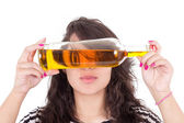 Latin girl hiding eyes behind a yellow bottle — Stock Photo