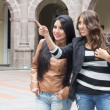 Two latin girls smiling and pointing a place — Stock Photo #49618513
