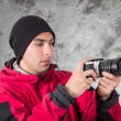 Closeup of young handsome man wearing red jacket and black beanie over grey background — Стоковое фото #49780843