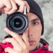 Closeup of young handsome man wearing red jacket and black beanie over grey background — Стоковое фото #49780989