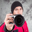 Closeup of young handsome man wearing red jacket and black beanie over grey background — Стоковое фото #49823147