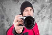 Closeup of young handsome man wearing red jacket and black beanie over grey background — Stock Photo